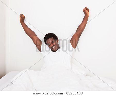 Young Man Waking Up At Bedroom