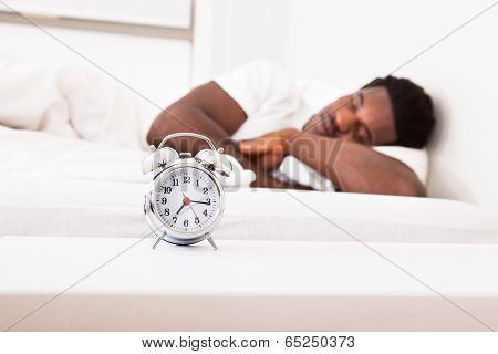 A Man Is Sleeping With An Alarm Clock