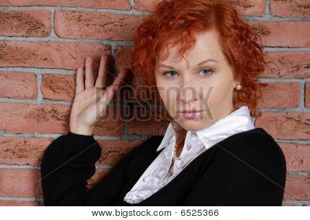Rothaarige junge Frau im Studio in der Nähe von Mauer