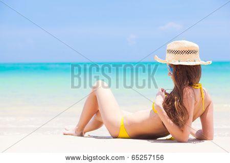 young beautiful woman in yellow bikini and straw sun hat relaxing at beach. Thailand, Khao Lak