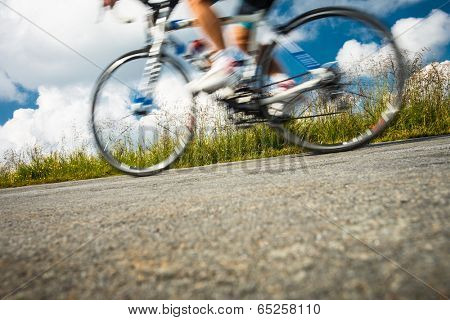 Motion blurred biker on a mountain road