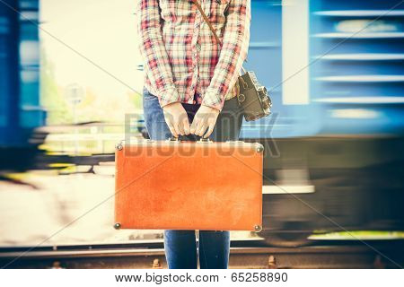 Young Woman With Retro Suitcase And Camera On Railway Platform