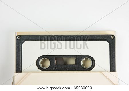 Early 70's cassette tape in sticking out from an open cassette case, on natural white background.