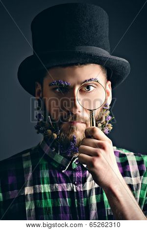 Strange young man with a beard of flowers wearing top hat and looking curiously through magnifier.