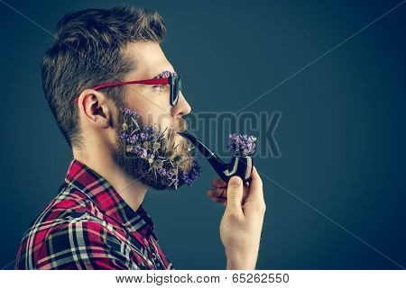 Handsome young man in glasses and a beard of flowers smoking a pipe. Profile portrait.