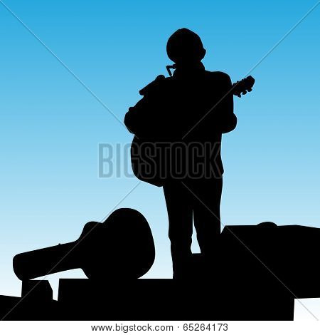 An image of a musican on stage playing a guitar and harmonica.
