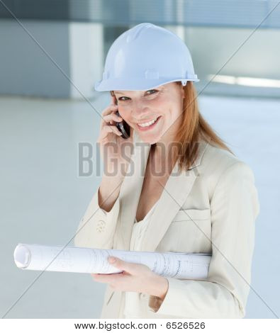 Smiling Female Architect With Hardhat On Phone