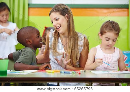 Smiling nursery teacher talking to african boy in kindergarten
