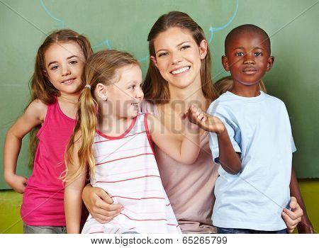 Happy woman with three different children in a kindergarten
