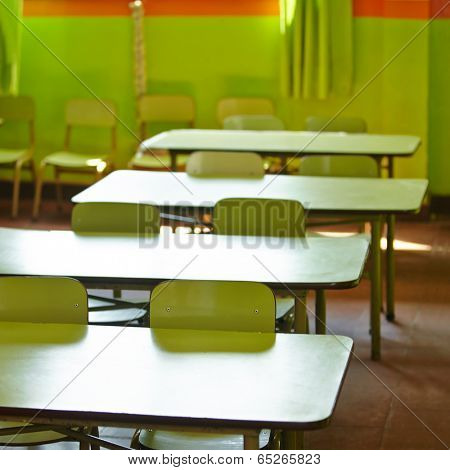 Empty classroom in a elementary school with tables and chairs