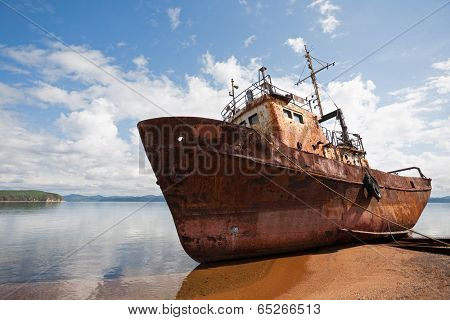 Old fishing vessel on the sea coast in sunny day.