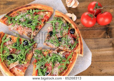 Pizza with arugula on color wooden background