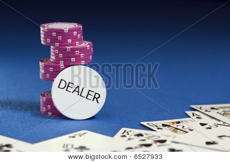 Dealer Button With Poker Chips And Playing Cards On Blue Felt.