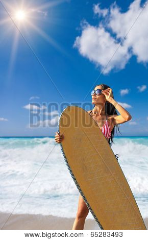 woman on the beach with surfboard.