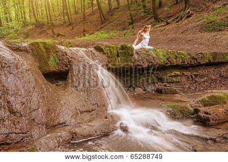 Relaxation Woman practices yoga at the waterfall