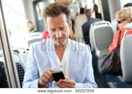 Mature man using smartphone in streetcar