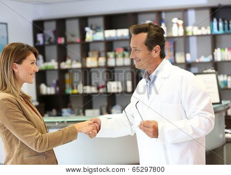 Veterinarian giving handshake to client