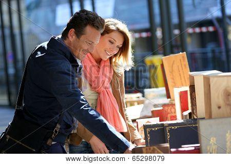 Loving couple walking by book fair on week-end