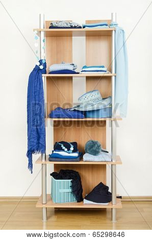 Blue clothes nicely arranged on a shelf.