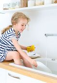 picture of diligent  - Happy little girl washing the dishes in the kitchen - JPG