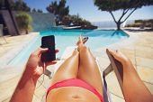 foto of pov  - Young woman holding a smart phone by the pool - JPG
