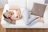 stock photo of stomach  - Portrait of woman with stomach ache sitting sofa - JPG