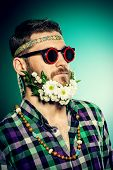 image of hippies  - Funny smiling young man in glasses and a beard of flowers - JPG