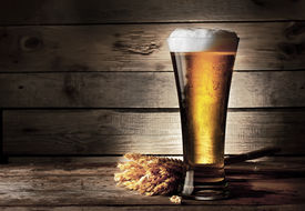 stock photo of beaker  - Tall beer glass with beer on wooden background  - JPG