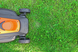 stock photo of grass-cutter  - top view of electric lawnmower on green grass - JPG