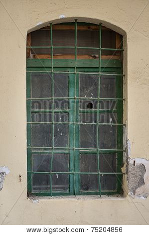 Old green window with broken glass
