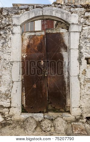 Old white rusty door in the scuffed wall