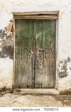 Old green timber door in the scuffed wall