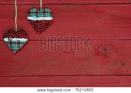 Country fabric Christmas hearts hanging from rope against antique red wood background