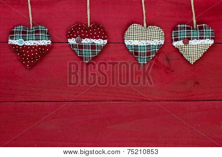 Country fabric Christmas hearts hanging from rope on antique red rustic wood background