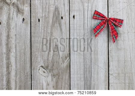 Plaid Christmas bow on rustic wood background