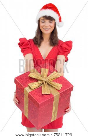Festive brunette giving a gift on white background