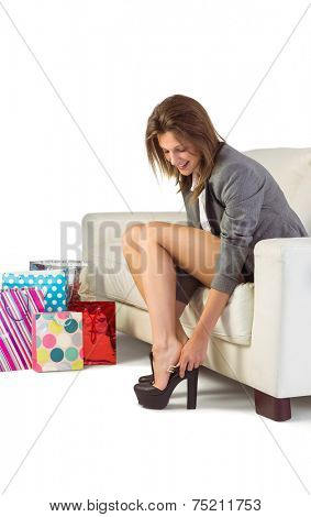 Young woman sitting on couch taking off her shoes at home in the living room