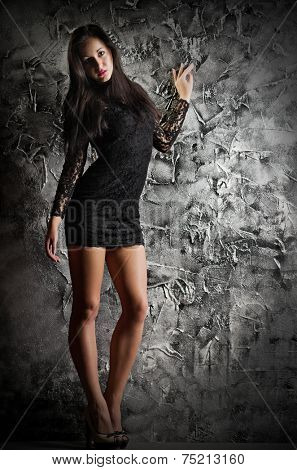 Fashion style portrait of young girl on grey wall