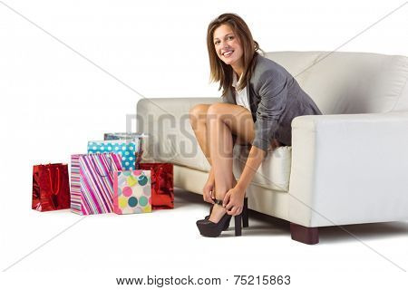 Well dressed woman sitting on couch taking off her shoes at home in the living room