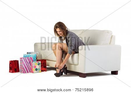 Cute woman sitting on couch taking off her shoes at home in the living room