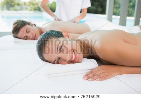 Side view of a young couple enjoying massage at health farm