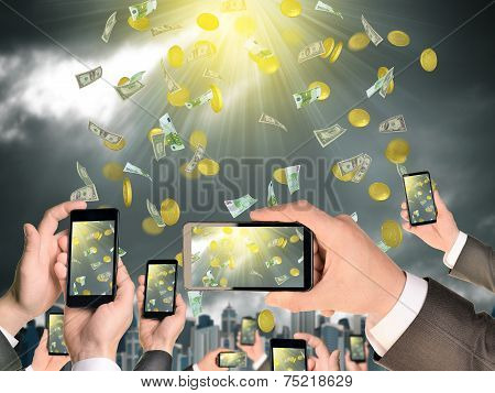 Hands holding smart phones and shoot video as falling money