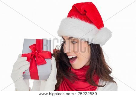 Astonished brunette in santa hat showing gift on white background