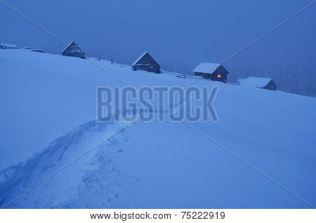 Evening landscape. Trail in the snow. Light in the window of a wooden house. Winter in the mountain village. Carpathians, Ukraine