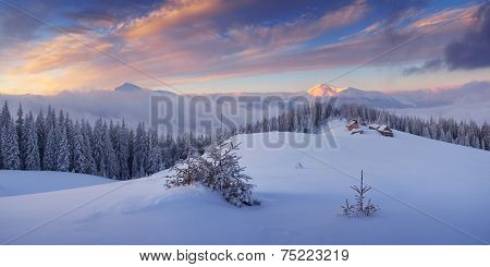 Winter landscape in the mountains. Frosty morning with a beautiful sky. The village of shepherds on a mountain meadow. Carpathians, Ukraine