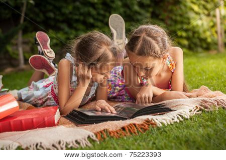 Girls Lying On Grass At Park And Looking At Old Family Photos