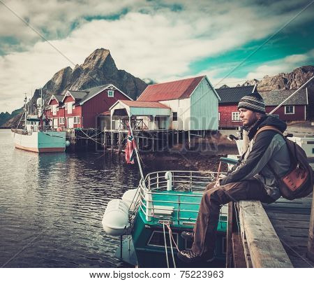 Man traveller sitting on a pier in Reine village, Norway
