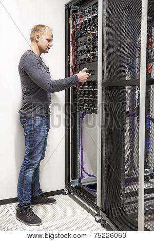IT engineer building network rack in datacenter