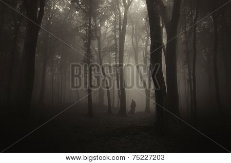 Ghost in mysterious dark forest with fog