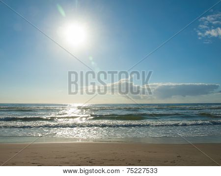 Ocean Waves Breaking On The Beach As The Sun As The Going Down